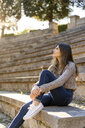 Young woman sitting on stairs outdoors looking around - AFVF02437