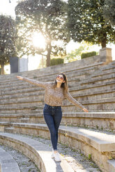 Happy young woman balancing on stairs outdoors - AFVF02440
