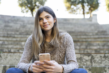 Young woman sitting on stairs outdoors holding cell phone - AFVF02452