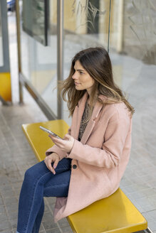 Young woman with cell phone waiting at bus stop - AFVF02464