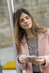 Young woman with cell phone waiting at bus stop - AFVF02467