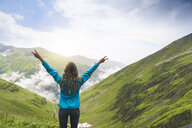 Happy woman raising her arms and looking over the Carpathian Mountains, Romania - SBOF01816
