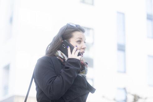 Junge Frau mit Mantel, Handy und Sonnenbrille vor Häusern - SGF02231