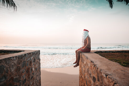 Thailand, man dressed up as Santa Claus sitting on wall in front of the sea watching sunset - HMEF00209