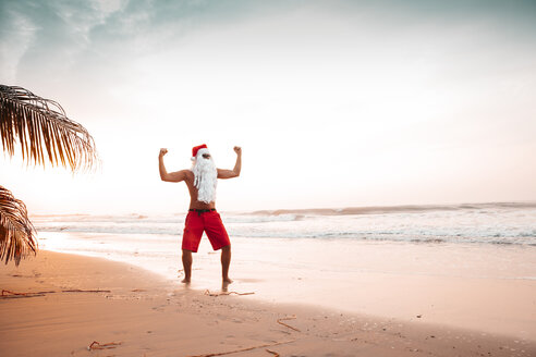 Thailand, man dressed up as Santa Claus posing on the beach at sunset - HMEF00212