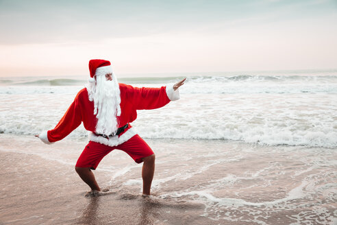 Thailand, man dressed up as Santa Claus posing on the beach at sunset - HMEF00215
