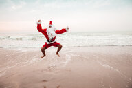 Thailand, man dressed up as Santa Claus jumping in the air on the beach - HMEF00218