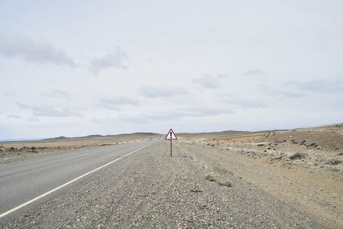 Argentina, Patagonia, Empty road with exclamation mark sign in the middle of desert - IGGF00788