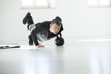 Man doing his fitness regime, doing kettle bell push-ups - MAEF12801