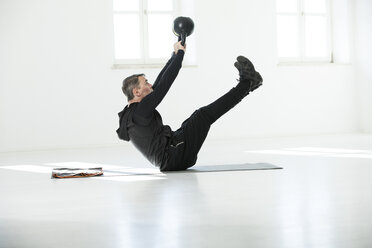 Man doing his fitness regime, doing kettle bell sit-ups - MAEF12804