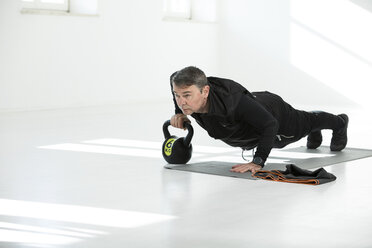 Man doing his fitness regime, doing kettle bell push-ups - MAEF12807