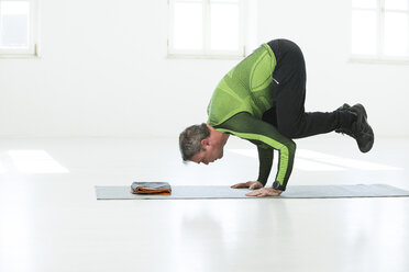Man doing his fitness regime, practising yoga poses - MAEF12816