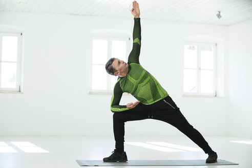 Man doing his fitness regime, practising yoga poses - MAEF12819