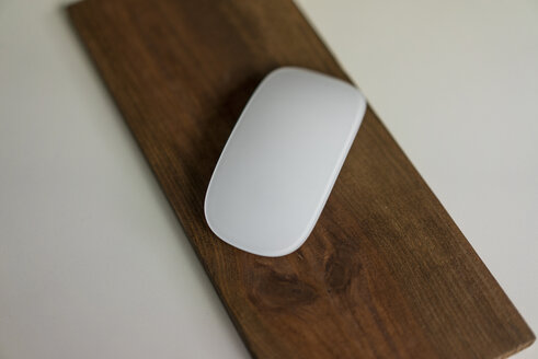 Computer mouse on wooden board on a desk - MOEF02018
