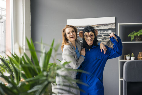 Businesswoman standing in office with a trainee, wearing monkey mask and blue oevrall - MOEF02036