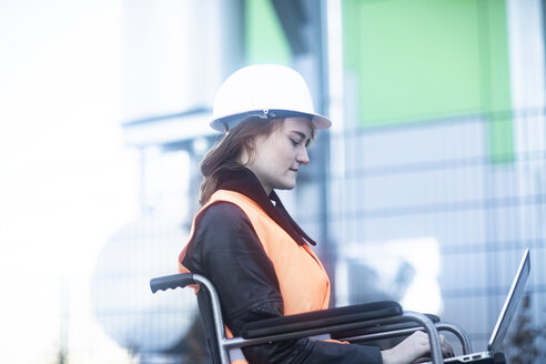 Young technician with safety helmet and vest in wheelchair working on laptop outdoors - SGF02249