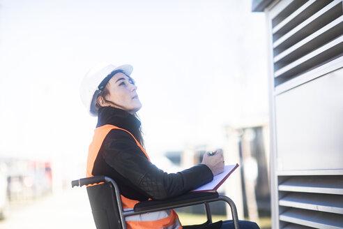 Junge Technikerin mit Helm im Rollstuhl arbeitend aussen - SGF02252