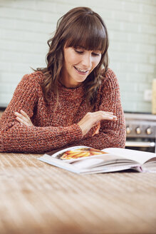 Mature woman sitting in kitchen, reading book - MCF00005