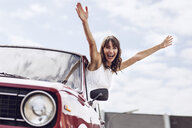Cheering woman looking out of vintage car - MCF00017
