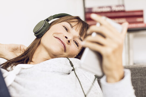 Woman lying couch, listening music with headphones - MCF00059