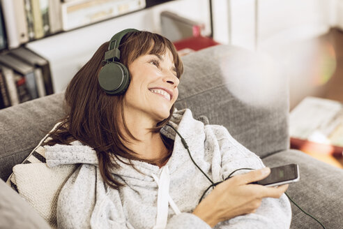 Woman lying couch, listening music with headphones - MCF00062