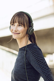 Sportive woman with headphones, doing her fitness training outdoors - MCF00086