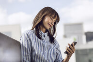 Businesswoman reading messages on her smartphone, outdoors - MCF00092