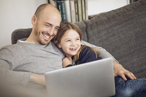Father and daughter sitting on couch, using laptop - MCF00098