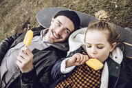 Father and daughter resting on skateboard, eating ice cream - MCF00104