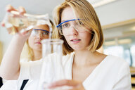 Young university student performing science experiment in laboratory - ASTF03990