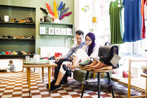 Man looking at woman trying shoe in store - ASTF04119
