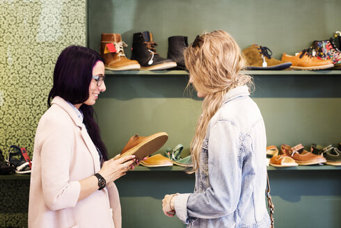 Young women shopping for shoes in a boutique - ASTF04128