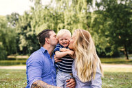 Parents kissing happy son - ASTF04191