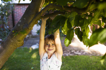 Portrait of happy girl hanging from branch in backyard - ASTF04194