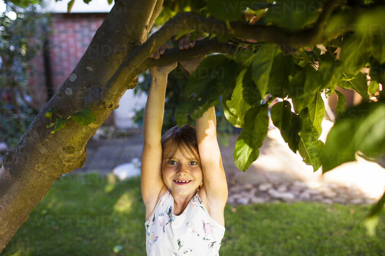 Portrait of happy girl hanging from branch in backyard - ASTF04194 - Astrakan Images/Westend61