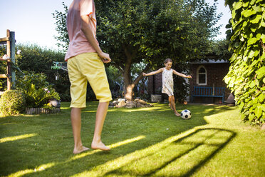 Brother and sister playing soccer in backyard - ASTF04203