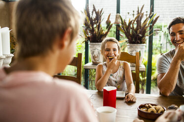 Happy girl having cookie while having breakfast with family at home - ASTF04224