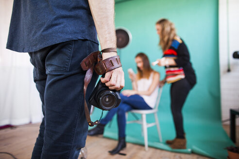 Midsection of photographer holding digital camera while models getting dressed in background at studio - ASTF04245