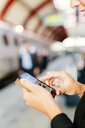 Cropped image of businesswoman using smart phone at central station - ASTF04296
