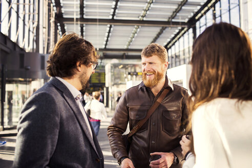 Happy businessman discussing with colleagues at railroad station - ASTF04326