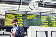 Low angle view of businessman using smart phone at railroad station - ASTF04329