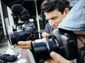 Close-up of photographer using digital cameras outdoors - ASTF04359