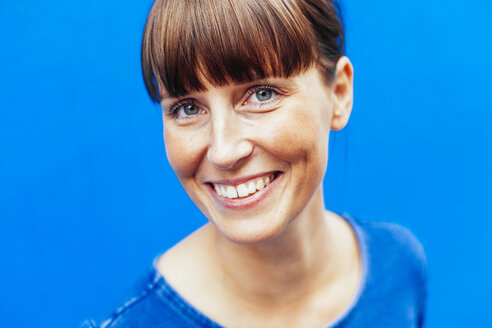 Close-up portrait of happy woman against blue background - ASTF04365