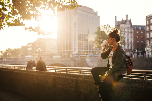 Woman drinking coffee while sitting retailing wall of bridge in city - ASTF04374