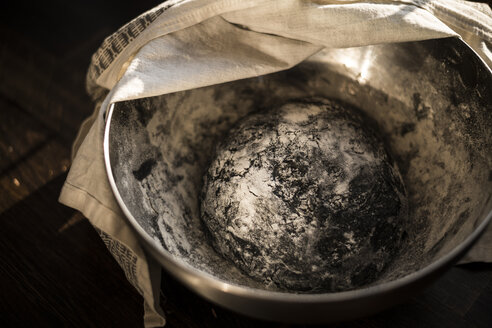Black dough for burger buns rising in a bowl - MJRF00004