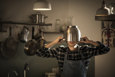 Man with apron standing in kitchen, wearing colander as helmet - MJRF00007