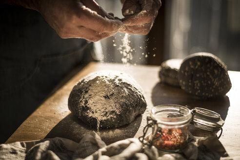 Man preparing black burger buns in kitchen - MJRF00010