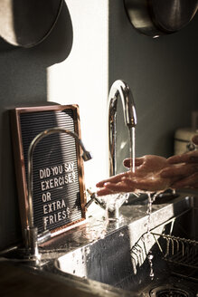 Board with funny text at the kitchen sink, where a man is washing his hands - MJRF00055