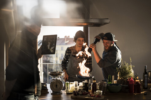 Friends flambeing food in a pan, producing a big flame, while friend is filming - MJRF00058