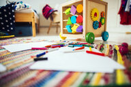 Colored pencils and drawing papers on carpet at home - ASTF04420